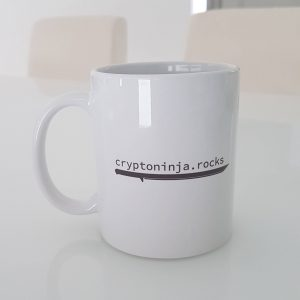 Eine weisse cryptoninja Tasse auf einem weissen Glastisch mit hellem Hintergrund