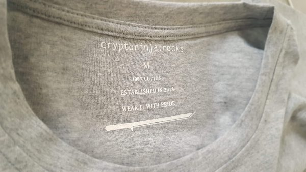 The cryptoninja inside print with the t-shirt size on a grey textile